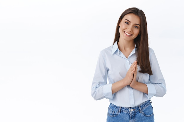 Bellissima giovane donna dall'aspetto amichevole pronta ad aiutare il cliente con qualsiasi problema, stringere le mani vicino al petto e inclinare la testa ascoltando con piacere, sorridendo dire per favore o essere grata per il favore