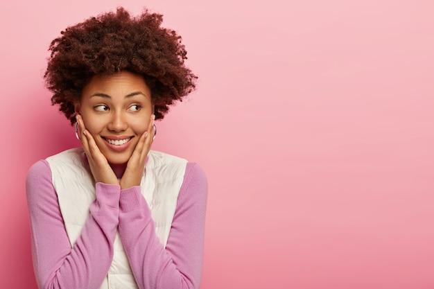 Приветливая счастливая афроамериканка смотрит в сторону с улыбкой и удивлением, касается ладонями обеих щек, носит фиолетовый джемпер и белый жилет, с теплым нежным выражением лица, изолирована на розовой стене