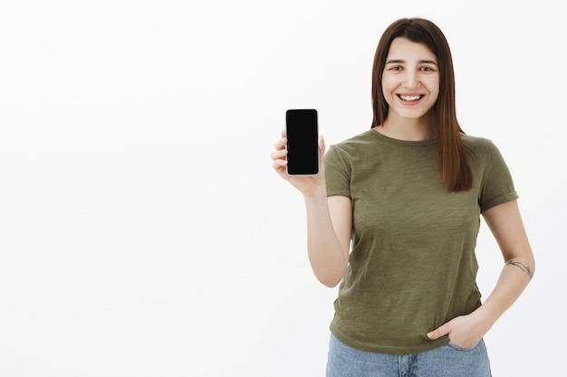灰色の壁を越えて携帯電話の画面上にスマートフォンプレゼンテーションアプリを保持しているように微笑し、優しく笑っているカジュアルなオリーブのtシャツの入れ墨をしたフレンドリーな外観の楽しくてのんきな若い20代ブルネット