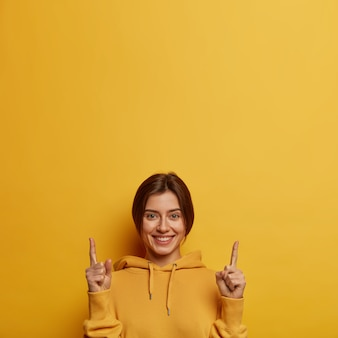 Friendly looking lovely woman shows promo with joy, points above with both index fingers, gives recommendation or advice, wears yellow hoodie