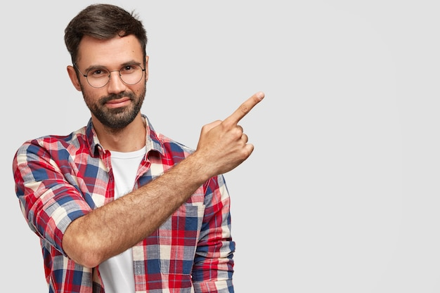 Venditore maschio dall'aspetto amichevole con setola, vestito con abiti alla moda, punti nell'angolo in alto a destra