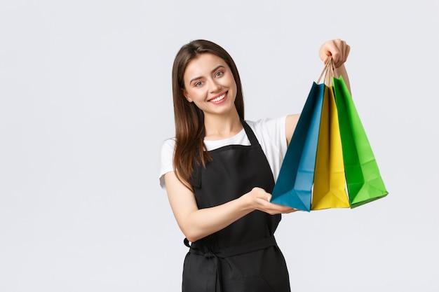 Приветливая милая женщина-кассир, приятно улыбается и передает покупателю сумки с купленными товарами, желаю хорошего дня. кассир работает, порядок обработки, белый фон.