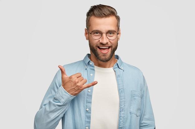 Hipster positivo dall'aspetto amichevole con stoppia scura, gesti al coperto, mostra il segno di shaka, essendo di alto spirito