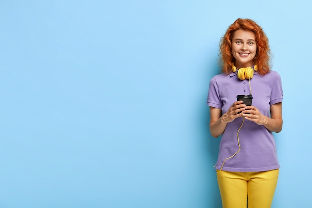 Friendly looking redhead woman holds disposable cup of coffee, drinks refreshing beverage in morning
