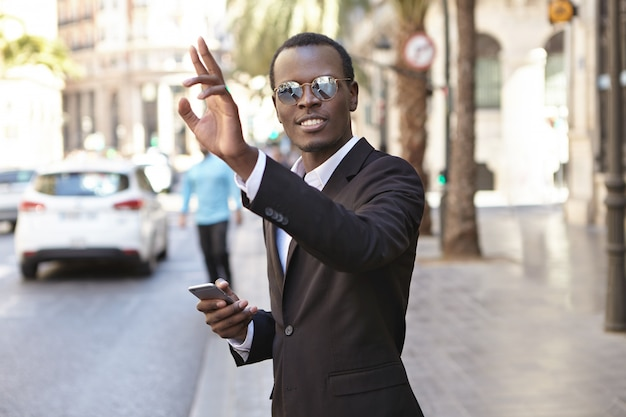 Friendly looking successful young afro american entrepreneur in elegant black suit and eyewear texting on cell phone and raising hand while hailing up cab, standing on street in urban surroundings