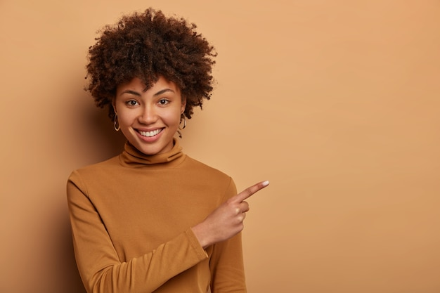 Friendly looking woman with afro haircut, points right on copy space, demonstrates new product, advertises something nice on sale