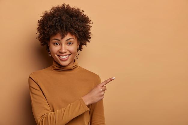 아프로 머리를 가진 친절하고 보이는 여성, 복사 공간에 바로 포인트, 신제품 시연, 판매시 좋은 광고 광고