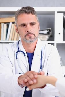 優しい男性医師が女性の腕を保持