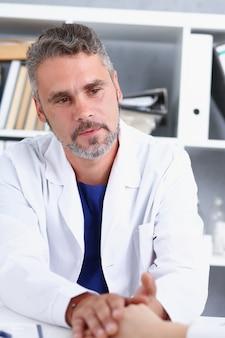 フレンドリーな男性医師は女性の腕を保持します