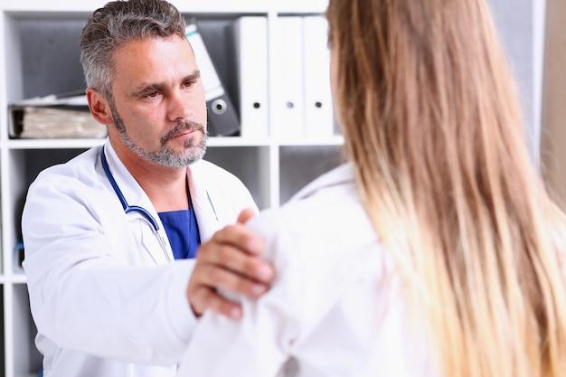 フレンドリーな男性医師がオフィスで患者の肩を保持します。