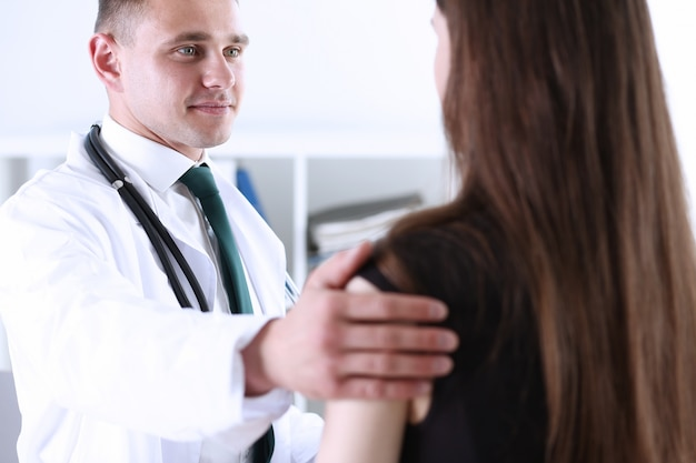 Friendly male doctor hold patient shoulder in office
