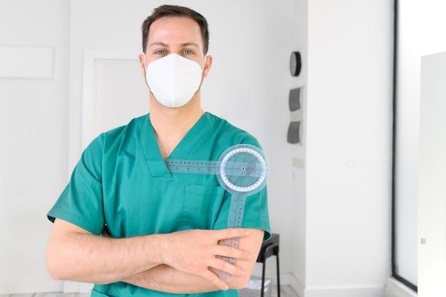 코로나 바이러스 전염병 동안 보호 얼굴 마스크를 착용하는 현대 병원에서 도구로 포즈를 취하는 친절한 남성 물리 치료사