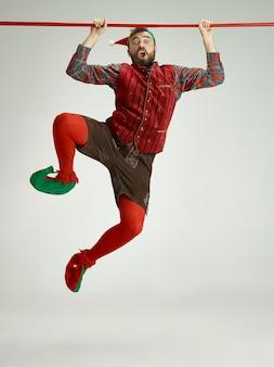 Дружелюбный мужчина, одетый как забавный гном, позирует на изолированном сером