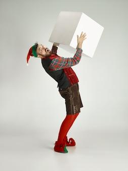 Дружелюбный мужчина в костюме забавного гнома позирует на изолированном сером фоне
