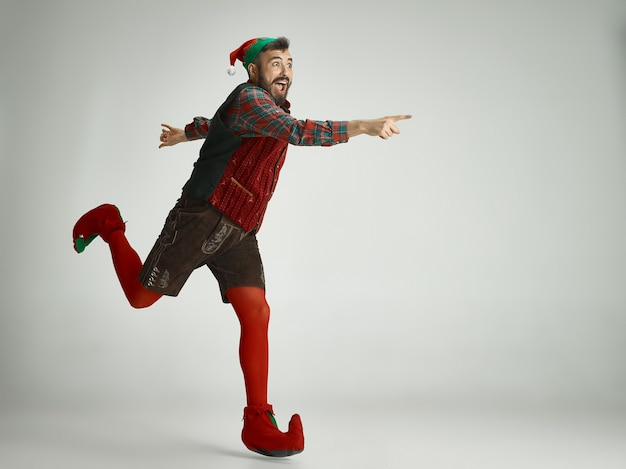 Friendly man dressed like a funny gnome posing on an isolated gray