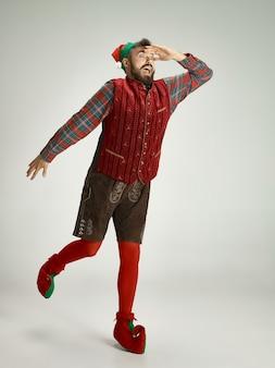 Uomo amichevole vestito come uno gnomo divertente in posa su un grigio isolato