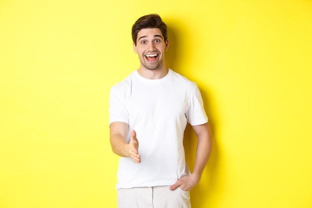 Friendly man greeting you with handshake, smiling amused, saying hello, standing over yellow wall
