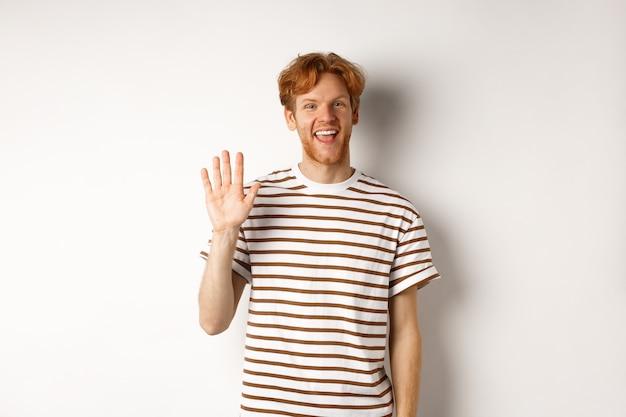 Дружелюбный мужчина с рыжими волосами и бородой здоровается, машет рукой и улыбается, стоя на белом фоне