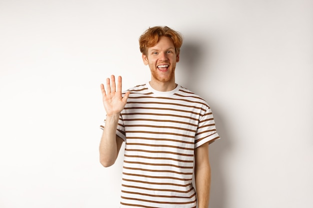 Friendly man with red hair and beard saying hi, waving hand and smiling, standing over white background