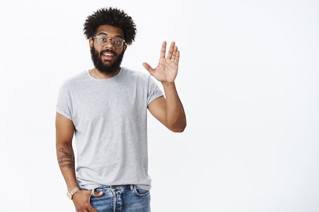 Дружелюбный зрелый афро-американский друг встречает друга на улице, наклонив голову, машет ладонью и здоровается, делая приветственный жест, счастливо улыбаясь, небрежно позирует над серой стеной