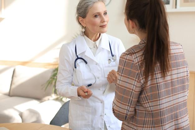 친절한 중년 여성 의사가 진찰 후 환자를 격려하고 지원합니다.
