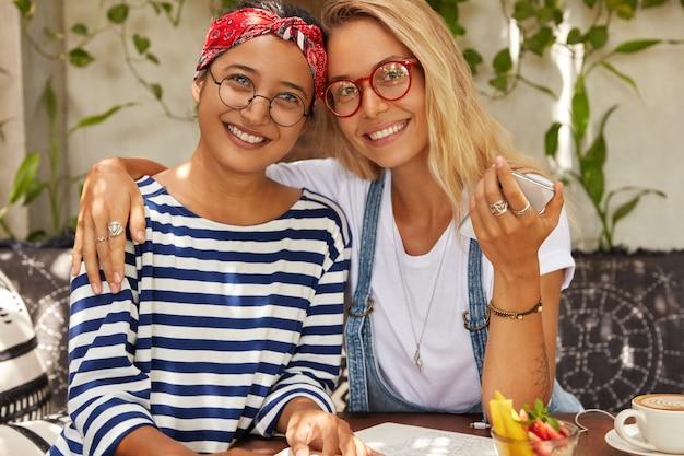 Amichevoli donne di razza mista con espressione positiva, si abbracciano mentre trascorrono il tempo libero in mensa, indossano occhiali