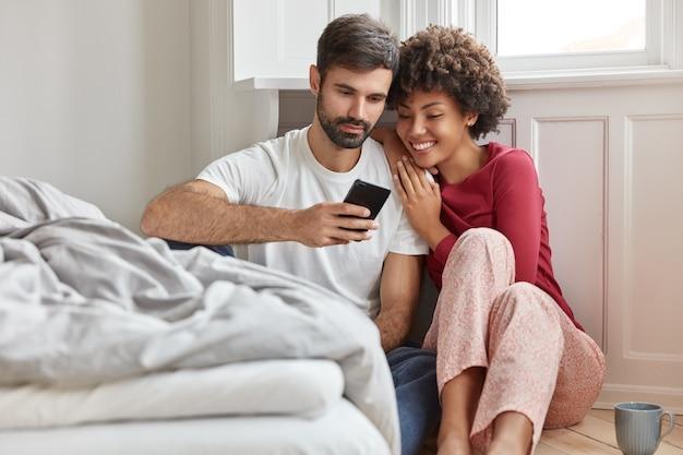Amichevole donna multietnica, uomo legge del testo o notizie positive in internet sul cellulare, vestito con abiti domestici casual, si siede sul pavimento vicino al letto, connesso a internet wireless, tempo di ricreazione