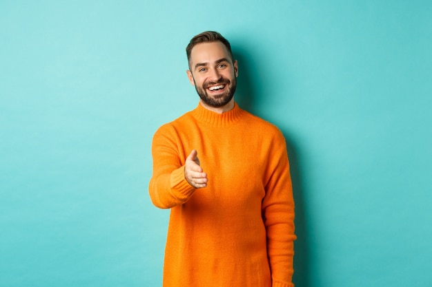 Friendly nice guy extend hand for handshake, greeting you and smiling, saying hello, standing over light blue background.