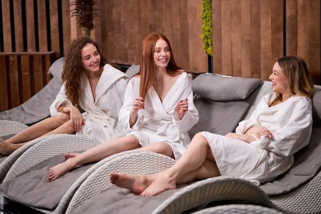 친절하고 멋진 여성들이 서로를 즐겁게하고, 스파 센터에서 이야기하고 웃으며, 미용 절차를받은 후, 흰색 목욕 가운을 입고 있습니다. 리조트에서 편안한 쾌활한 숙녀