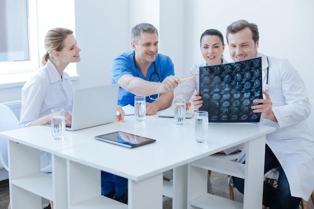 Дружелюбно занятые радостные рентгенологи работают в лаборатории и изучают результаты рентгеновского снимка мозга, наслаждаясь беседой и используя цифровые гаджеты.