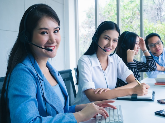 Friendly operator team agent with headsets working in a call centre
