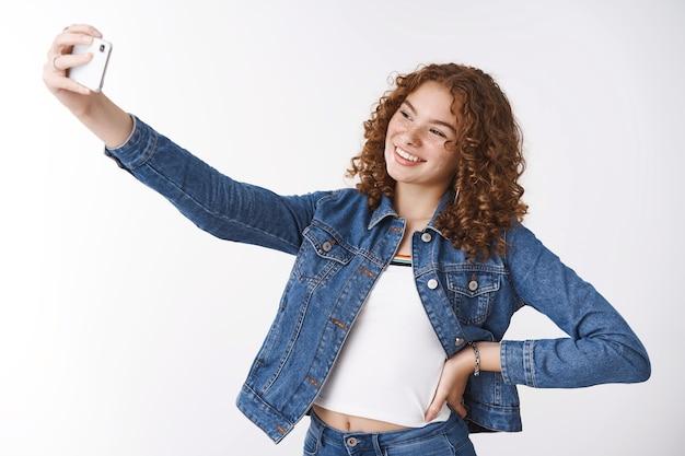 フレンドリーな発信魅力的な若い赤毛の巻き毛の女の子のにきびとそばかすは手腰を自信を持って腕を伸ばす自撮り新しいスマートフォンカメラ笑顔ガジェットディスプレイ立っている白い背景