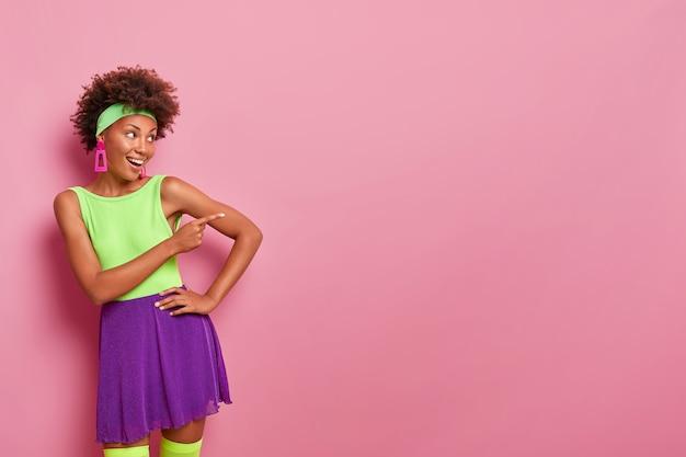 La donna afroamericana allegra in uscita amichevole in abiti luminosi punta proprio su uno spazio vuoto che si diverte e partecipa a una conversazione vivace, dà consigli e consigli per controllare la pubblicità