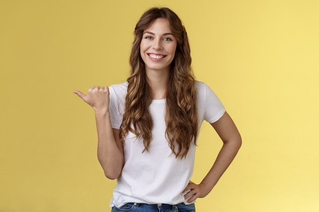 친절하고 나가는 쾌활한 유럽의 귀여운 여성이 방향을 제시하는 팁을 주는 활기찬 미소 이빨이 행복하게 왼쪽 엄지손가락을 가리키는 좋은 즐거운 대화를 나누며 프로모션 노란색 배경을 소개합니다.