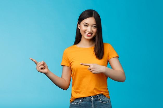 Дружелюбная общительная симпатичная азиатская женщина показывает промо, указывая влево, указывая пальцами на рекламу, дает совет, уверенно улыбается, приятно помогает подобрать одежду, стоит на синем фоне.