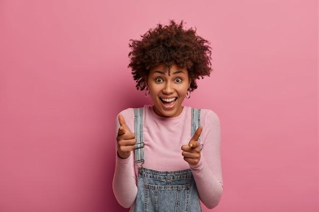 フレンドリーな外向的な女性は、良い仕事を称賛するように指ピストルのジェスチャーをし、成功した試験と達成でグループメートを祝福し、心から笑い、ピンクでポーズをとります。