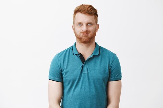 フレンドリーで遊び心のある、のんきな赤毛の成熟した白人の男は、口の中で息を止め、幼稚な表情と笑顔でふくれっ面をして、灰色の壁を騙している