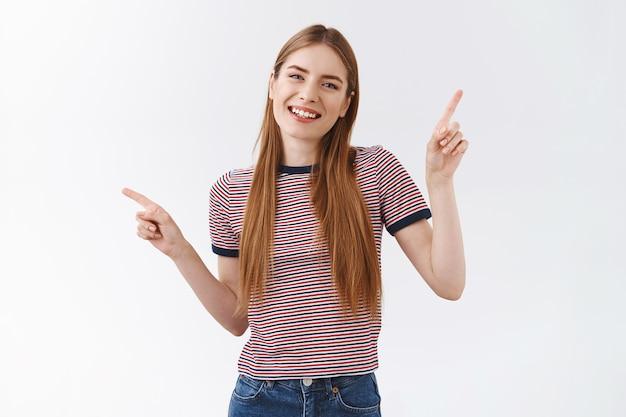 긴 머리에 줄무늬 티셔츠를 입은 친절하고 유쾌한 쾌활한 여성, 옆으로 가리키는 손을 들고, 왼쪽 및 오른쪽 선택 제품을 보여주고, 기쁘게 웃고, 제안을 합니다.