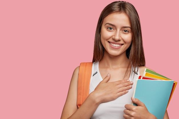 ピンクの壁に向かってポーズをとるフレンドリーで喜んでいる学生