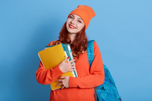 Friendly pleased young lady in cap carries rucksack, holds paper folder with papers