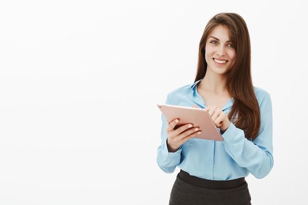 Donna di affari bruna educata amichevole in posa in studio