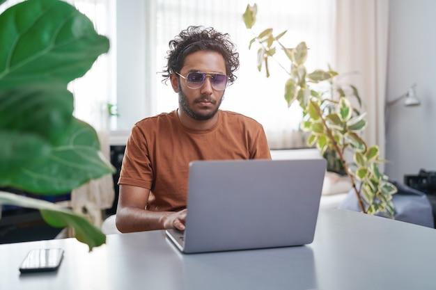 彼はデスクトップに座って、自宅で昼間にラップトップで仕事をしているインドのプロのマネージャーのフレンドリーな肖像画。