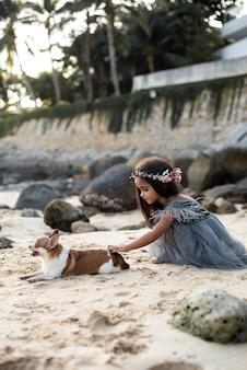 タイでの休暇で一緒に楽しい時間を過ごしている海岸の就学前の女の子と彼女のペットのフレンドリーな肖像画。