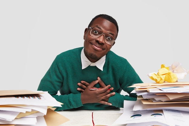 Friendly positive black man keeps hands on chest, holds pen, has pleased facial expression, being thankful to friend for helping with paper work