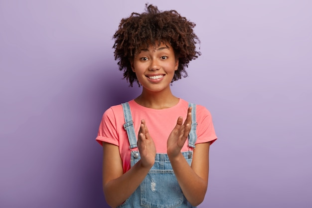 Friendly positive female claps hands, applauds friend or colleague who achieved great success