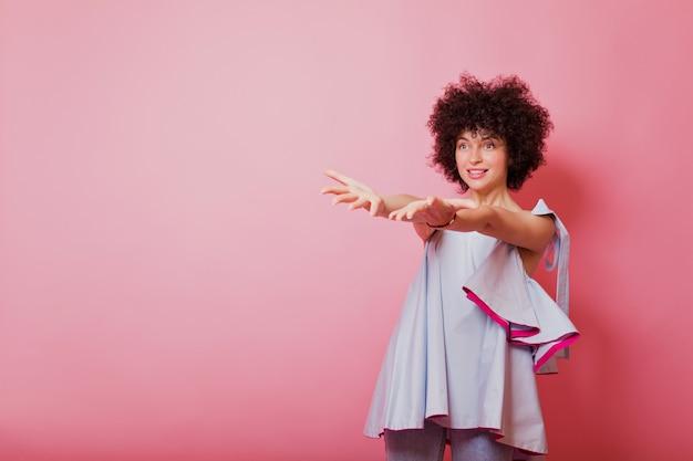 파란색 셔츠를 입은 어두운 짧은 머리를 가진 친절한 예쁜 여자가 그녀의 손을 위로 끌어 올리고 분홍색을 가리 킵니다.