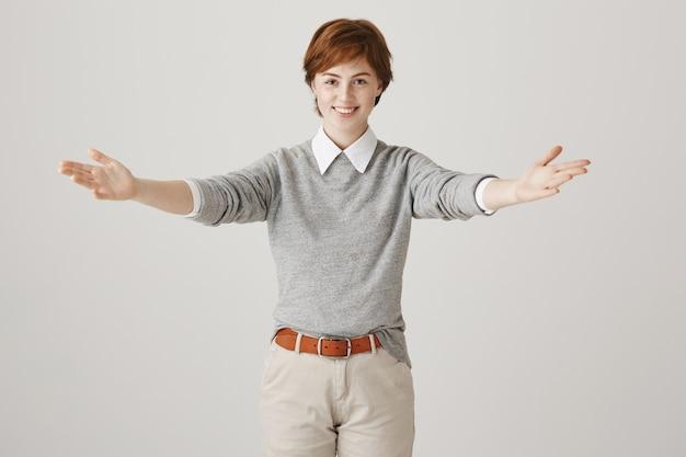 짧은 머리는 흰 벽에 포즈와 친절한 빨간 머리 소녀