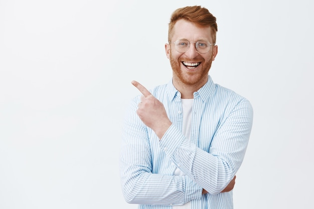 Friendly redhead man with bristle in transparent glasses and striped shirt pointing at upper left corner, smiling broadly with satisfied and pleasant look