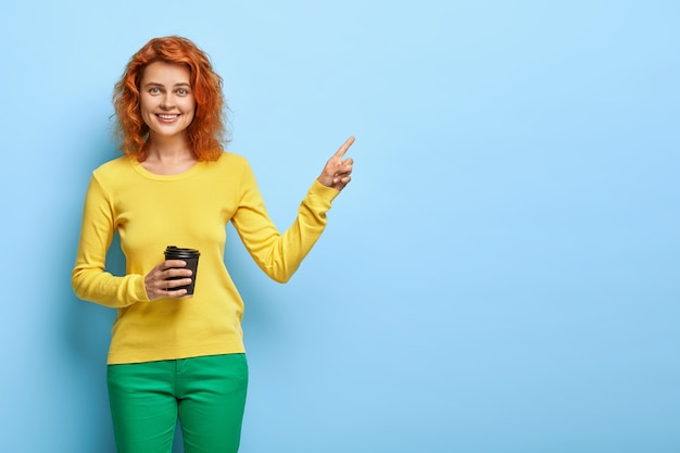 Friendly redhead woman holds disposable cup of cappuccino, shows way to coffee shop, wears fashionable clothes
