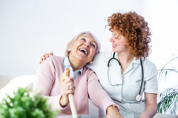 制服を着た介護者の笑顔と幸せな高齢女性の友好関係。年配の女性を見て協力的な若い看護婦さん。